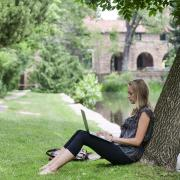 Grad student leans against a tree while working on laptop
