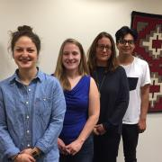 Three students and Carla Fredericks, all involved in the project, stand in a row, posing for a snapshot with a red tribal tapestry handing on the wall behind them.