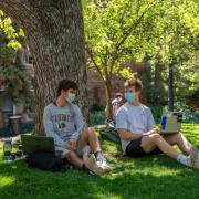 two people in masks talking on campus