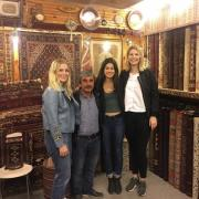 Three female college students pose with owner of carpet shop in Istanbul, Turkey