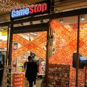 The window of a GameStop store with signs advertising a sale