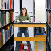 A student is surrounded by book shelves at Gemmill Library at CU Boulder