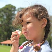 A girl eats a marshmallow.