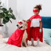 Girl and a dog dressed as heroes, standing on a bed