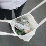 Person carrying empty glass bottles in a reusable bag