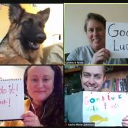 Libraries staff pose for virtual photo with 'good luck' signs