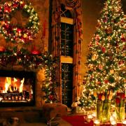 Brightly-lit Christmas tree with a warm fire in the fireplace