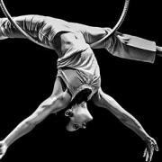 An aerial performer is highlighted in this black and white image
