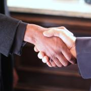 Black woman and white man shake hands