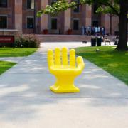 Bright yellow hand sculpture on campus