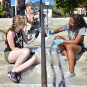 Two students re-painting handrails on The Hill