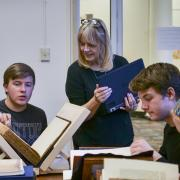Students in HIST 1113 Honors Seminar examine rare books and pamphlets at the Norlin Library Special Collections