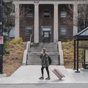 student with rolling suitcase departing campus for break