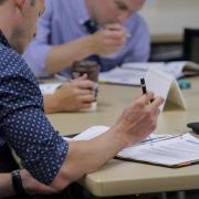 Man writes in workbook during HR supervisor class