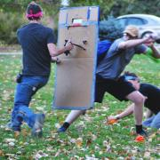 Human player blocks zombie players using cardboard shield