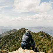 Man watches vista from mountain summit
