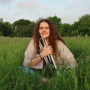 Anna Kallinikos, sitting in a field with her trumpet