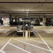 Car at EV charging station in parking garage