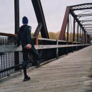 Runner stretches on pedestrian bridge