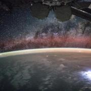 An image taken from the International Space Station shows orange swaths of airglow hovering in Earth's atmosphere