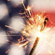 Sparkler in front of American Flag.