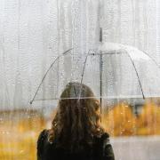person standing under umbrella alone in the rain