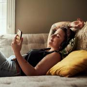 person lying on couch and scrolling on their phone