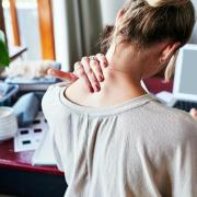 person rubbing neck while sitting at desk