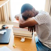 student sleeping on stack of books at desk