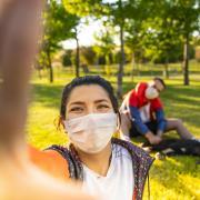 People wearing masks sitting outside