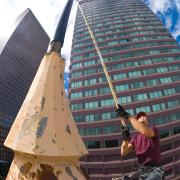 A worker is seen with a long pole, painting a flagpole in downtown Denver.