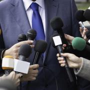 A stock photo of a press conference and reporters