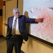 """Harrison """"Jack"""" Schmitt, a former NASA astronaut, points to a photograph of reddish-orange lunar soil that he took during his trip to the moon in 1972."""