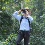Joanna Lambert standing on tree limb and looking through binoculars.
