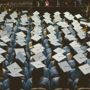 Graduates in caps and gowns sit facing stage at commencement ceremony