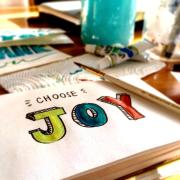 """An illustration of the word """"joy"""" is seen in a sketch book with a paintbrush nearby. (Photo by Bekka Mongeau from Pexels)"""