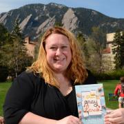 "Karstee Davis holding ""Eat Pray Love"" book in front of the Flatirons"