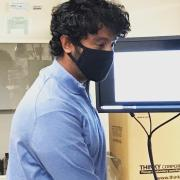 Assistant Professor Kaushik Jayaram works in the lab while wearing a mask