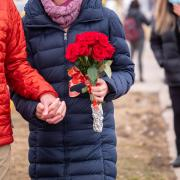 Two people, one of them carrying a bouquet of flowers, hold hands.