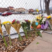 Flowers line a fence surrounding the parking lot where 10 adults, including a police officer, were shot by a lone gunman at the King Soopers at 3600 Table Mesa Dr. (Photo by Glenn Asakawa/University of Colorado)