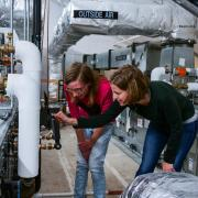 Two students checking the temperature and pressure settings for a rooftop HVAC unit in the Larson Laboratory (Photo via CU Boulder)