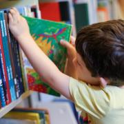 Child pulls a book from the shelf at the library