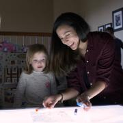 Researchers play with child over lighted table