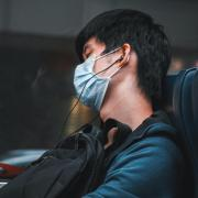 Person listening to music on a train in Taiwan while wearing a face mask