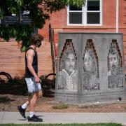 A person walks by the Los Seis de Boulder sculpture on the CU Boulder campus.