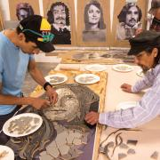 Artists work on part of a mosaic to commemorate 'Los Seis'