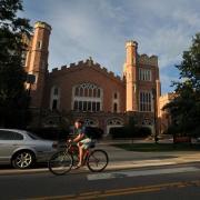 Students ride bikes past Macky Auditorium