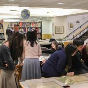 Students analyze maps in the library