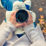 person holding cup of coffee while sitting outside in fall weather