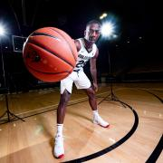 CU Boulder student athlete McKinley Wright holds a basketball on the court.